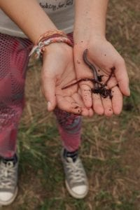 Menina mostra minhocas que vivem em pátio de compostagem. Foto: Cris Fontinha